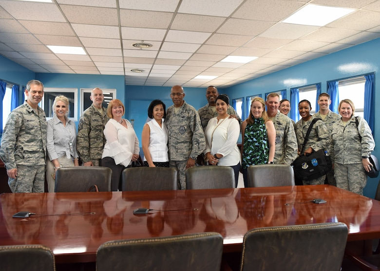 (Left to right) Lt. Gen. Kenneth Wilsbach, Seventh Air Force commander, his wife Cindy, Chief Master Sgt. Scott Lumpkin, Seventh Air Force command chief, his wife Meg, Gen. CQ Brown, Jr., Pacific Air Forces commander, his wife Sharene, Chief Master Sgt. Anthony Johnson, Pacific Air Forces command chief, his wife Stephanie, Lt. Gen. Thomas Bergeson, former Seventh Air Force commander, his wife Pamela, Capt. Lisa Gund, Seventh Air Force aide-de-camp, Brig. Gen. Lance Pilch, Seventh Air Force deputy commander, and Maj. Megan Mallone, 607th Air Operations Center legal advisor, pose for a photo inside a UNC Military Armistice Committee conference room at the Joint Security Area August 26, 2018. The room sits on top of the demarcation line, meaning the group is technically standing inside the Democratic People's Republic of Korea. (U.S. Air Force photo by Airman 1st Class Ilyana Escalona)