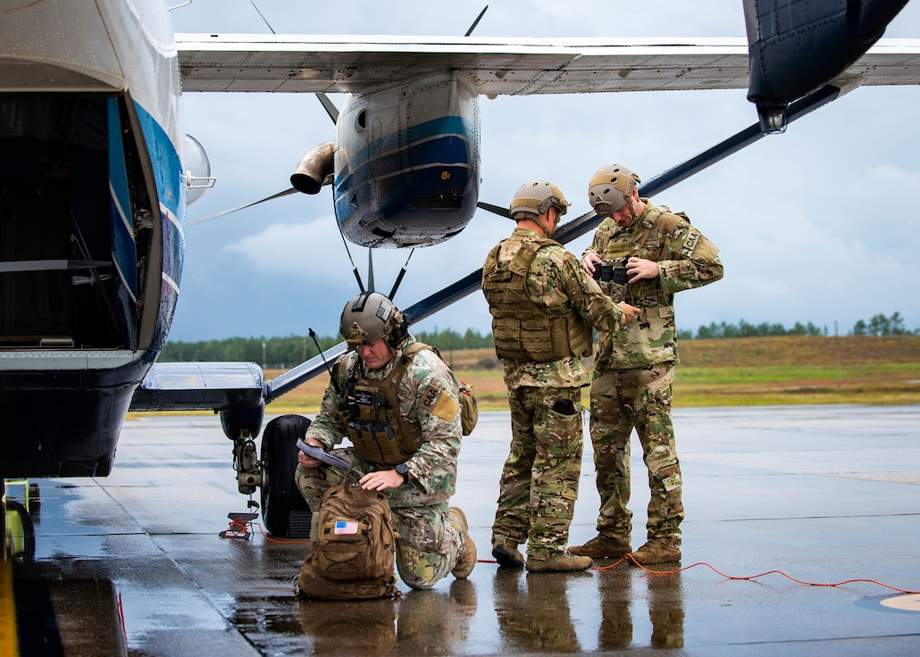 Master Sgt. Joseph Kimbrell (left) prepares his equipment for a future C-145A training mission while Master Sgt. Brian Schultz assists Tech. Sgt. Matthew Massey with adjustments to his pro gear. All are special mission aviators assigned to the 919th SOW.
