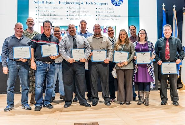A group of associates stand on stage with certificates for a photo