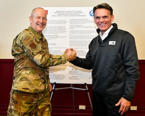 Brig. Gen. John D. Slocum, commander of Selfridge Air National Guard Base and the 127th Wing, and Macomb County Commissioner Mark Hackel, celebrate the 44th tenant organization joining the Team Selfridge Community after a key-passing ceremony here on November 14, 2018.