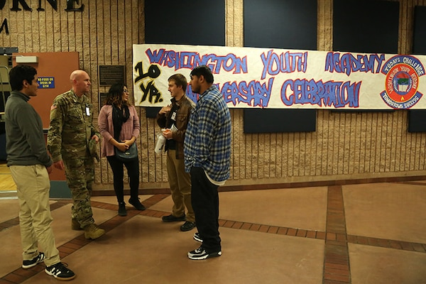Washington Youth Academy 1st Lt. Darrell Stoops talks with former graduates of the WYA during the academies 10-year anniversary ceremony Nov. 18, 2018, in Bremerton, Wash. The ceremony brought together former and current graduates as a way to reconnect with past graduates, as well as show the current class the success the program can lead to.