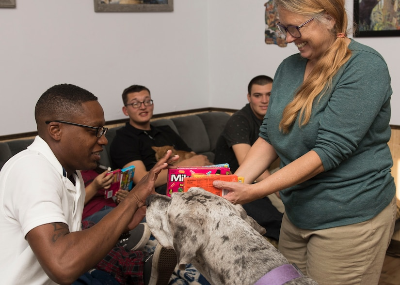U.S. Army Pvt. Jashun Coleman, 128th Aviation Brigade Advanced Individual Training student, picks a candy with the help of Shelby the dog in Newport News, Virginia, Nov. 22, 2018.