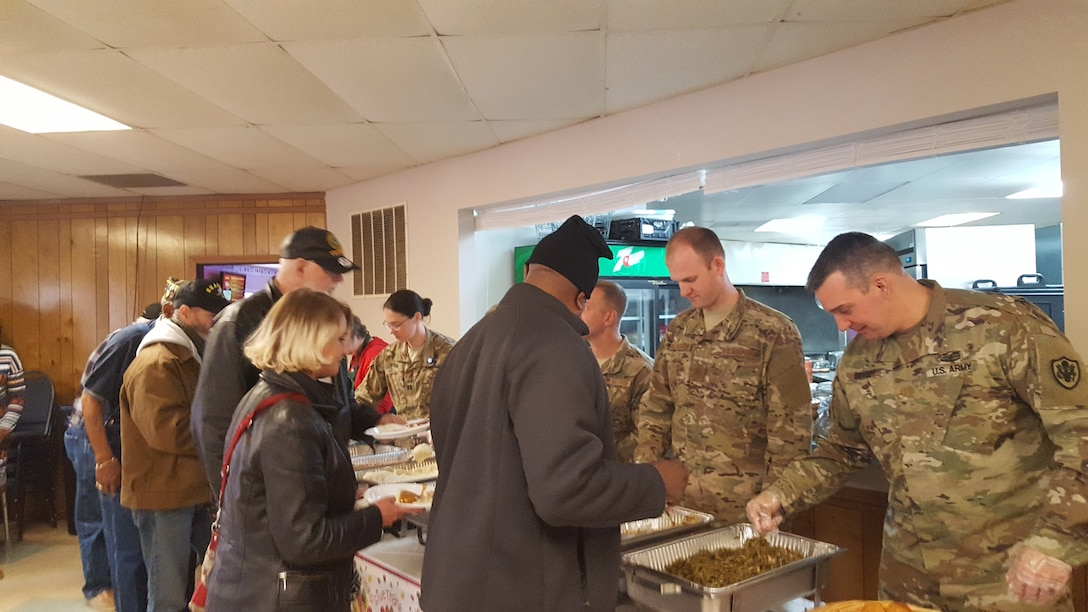Members of the military serve Thanksgiving dinner to veterans as they walk down the buffet line