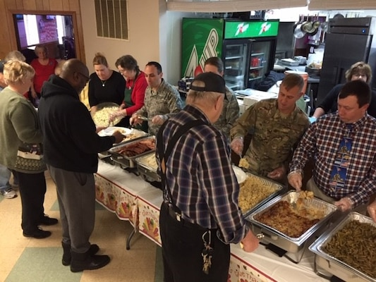Members of the military and civilian volunteers serve Thanksgiving dinner to veterans as they walk down the buffet line
