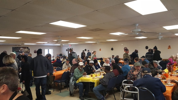 Veterans and military share a Thanksgiving meal together in a cafeteria style setting