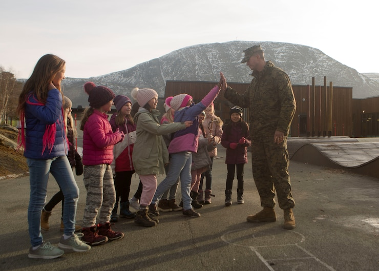 U.S. Marine Staff Sgt. Abraham Blocker with 4th Civil Affairs Group, 4th Marine Division, greets children at a local school during Exercise Trident Juncture 18 in Oppdal, Norway on Nov. 7, 2018. Trident Juncture 18 enhances the U.S. and NATO Allies' and partners' abilities to work together collectively to conduct military operations under challenging conditions. (U.S. Marine Corps photo by Cpl. Justin X. Toledo)