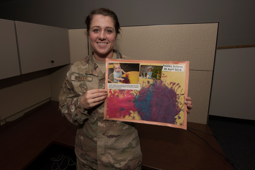 U.S. Air Force Staff Sgt. Amanda Scheer, 60th Contracting Squadron contracting specialist, poses for a photo in her office at Travis Air Force Base, California, while holding an original artwork her daughter Paisley created, Nov. 10, 2018. Scheer is a single mother and has served in the Air Force for six years. (U.S. Air Force photo by Tech. Sgt. James Hodgman)