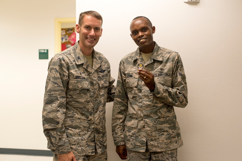 U.S. Air Force Col. Stephen Snelson, 6th Air Mobility Wing Commander, coins U.S. Air Force Airman 1st Class Daniel Kirwa, an aerospace medical technician assigned to the 6th Medical Operations Support Squadron, at MacDill Air Force Base's Brandon clinic, Fla., Oct. 11, 2018