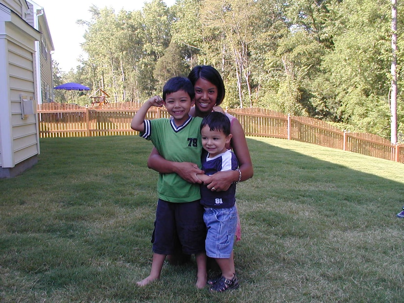 Woman and her two sons pose in backyard