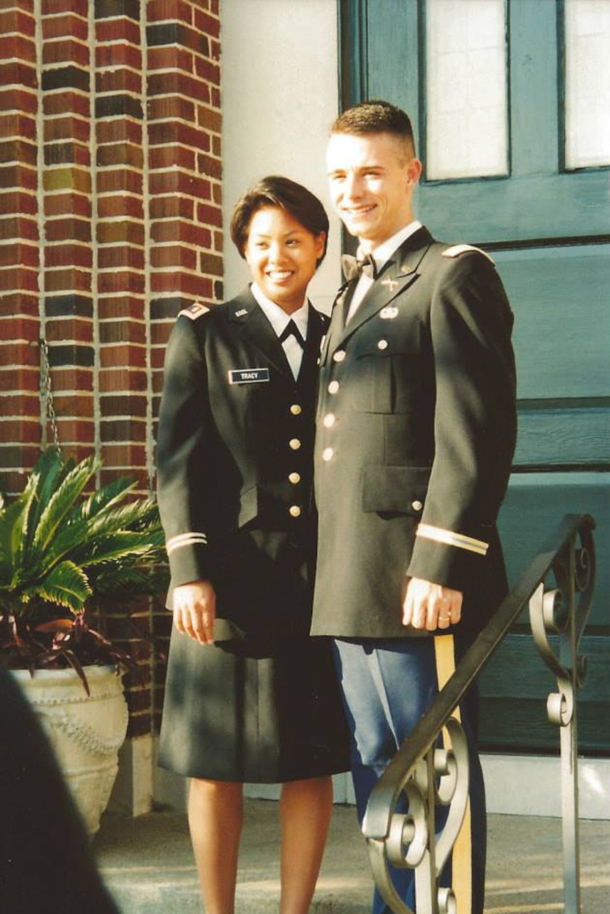 Man and woman pose on Army uniforms on steps