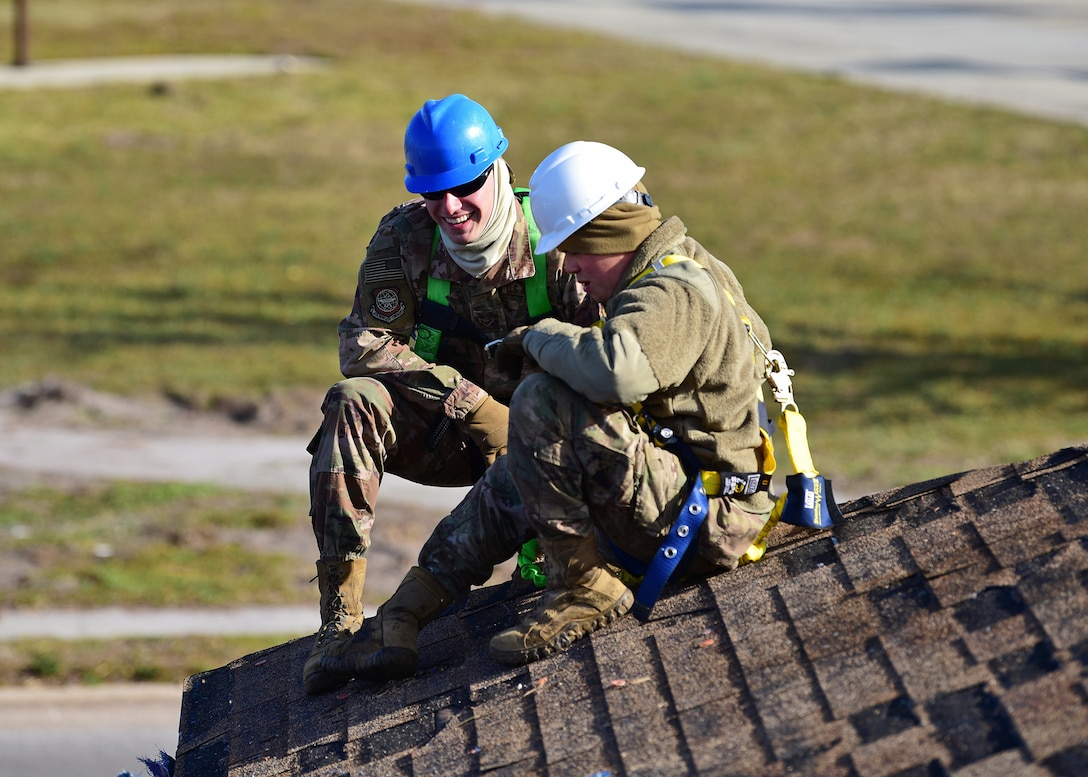 Task Force Phoenix members Airman 1st Class Marc Karns, left, and Senior Airman Jake Stauffer, right, pause for a moment while repairing a damaged rooftop at Tyndall Air Force Base, Fla., Nov. 28, 2018. Task Force Phoenix is tasked with large-scale cleanup and reconstruction of the base in the wake of Hurricane Michael. (U.S. Air Force photo by Senior Airman Isaiah J. Soliz)