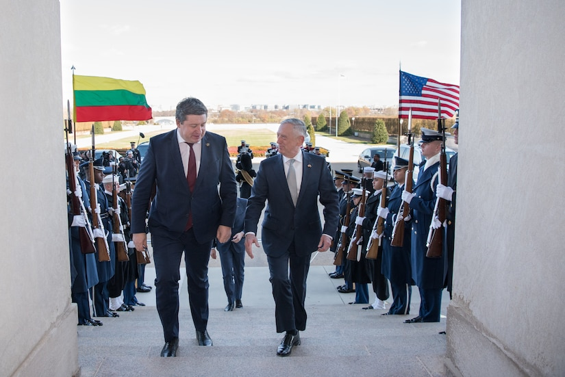 U.S. secretary of defense walks up steps with Lithuania's minister of defense