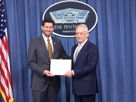 Defense Secretary James N. Mattis presents the citation for the Department of Defense Medal for Distinguished Public Service to House Speaker Paul Ryan in a Pentagon ceremony.