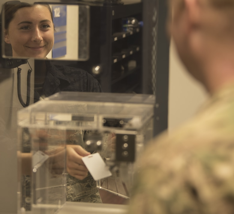 U.S. Air Force Senior Airman Charlotte Stenzel, 60th Air Mobility Wing Command Post emergency actions controller, provides a visitor pass Nov. 21, 2018, at Travis Air Force Base, California. The command post is in a secure location due to the types of information that they can receive, such as operational reports and their ability to track every flight that comes in and out of the base. (U.S. Air Force photo by Staff Sgt. Amber Carter)