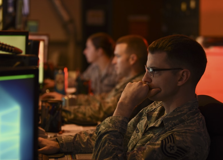 U.S. Air Force Tech. Sgt. Barron Dietrich, 60th Air Mobility Wing Command Post emergency actions controller, monitors his computer and Siemens communication console Nov. 21, 2018, at Travis Air Force Base, California. The command post tracks up to 30 flights per day at the largest base in Air Mobility Command. (U.S. Air Force photo by Staff Sgt. Amber Carter)