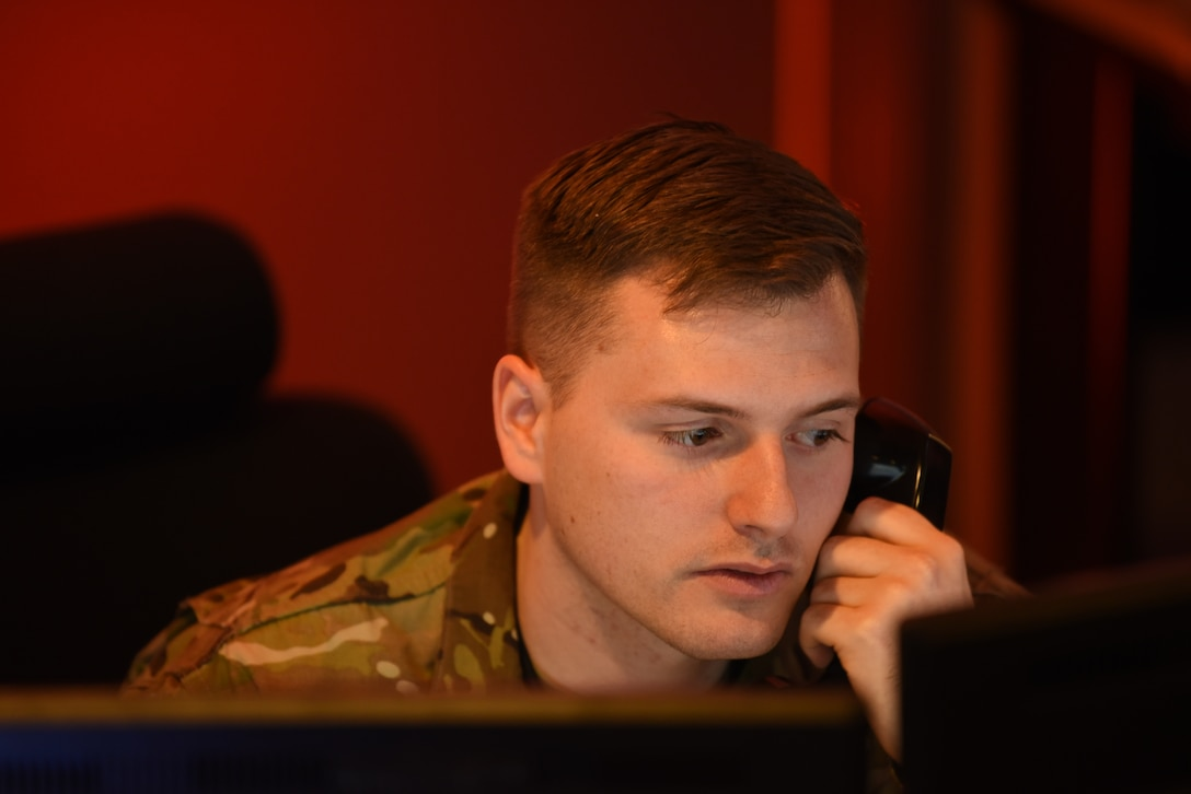 U.S. Air Force Staff Sgt. Jon Schexnyder, 60th Air Mobility Wing Command Post emergency actions controller, answers a phone call Nov. 21, 2018, at Travis Air Force Base, California. The command post can field more than 500 phone calls per shift requiring them to respond to a multitude of requests and incidents. (U.S. Air Force photo by Staff Sgt. Amber Carter)