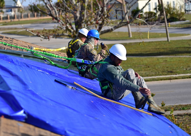 From left to right, Senior Airman Jake Stauffer and Airmen 1st Class Marc Karns and Ikiem Williams, members of Task Force Phoenix, repair a damaged rooftop at Tyndall Air Force Base, Fla., Nov. 28, 2018. Task Force Phoenix is responsible for large-scale clean up and reconstruction after Hurricane Michael ravaged Tyndall Air Force Base and the panhandle of Florida. (U.S. Air Force photo by Senior Airman Isaiah J. Soliz)