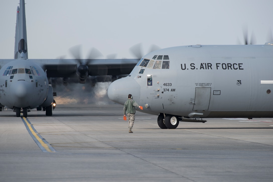 A crew chief, assigned to the 374th Aircraft Maintenance Squadron, marshals a C-130J Super Hercules during the 374th Airlift Wing Samurai Surge at Yokota Air Base, Japan, Nov. 29, 2018.