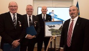 From left to right, Col. Lars-Erik Blad, Maj. Roger Moller, Maj. Krister Sjober, and Retired U.S. Air Force Lt. Col. Tom Veltri stand beside the official photo which depicts the event that earned the Swedish pilots their U.S. Air Medals in Stockholm, Sweden, Nov. 28, 2018. The Swedish Airmen risked their lives to save an SR-71 and the aircrew, Tom Veltri and Duane Noll, on June 29, 1987. (U.S. Air Force Photo by Senior Airman Kelly O'Connor)