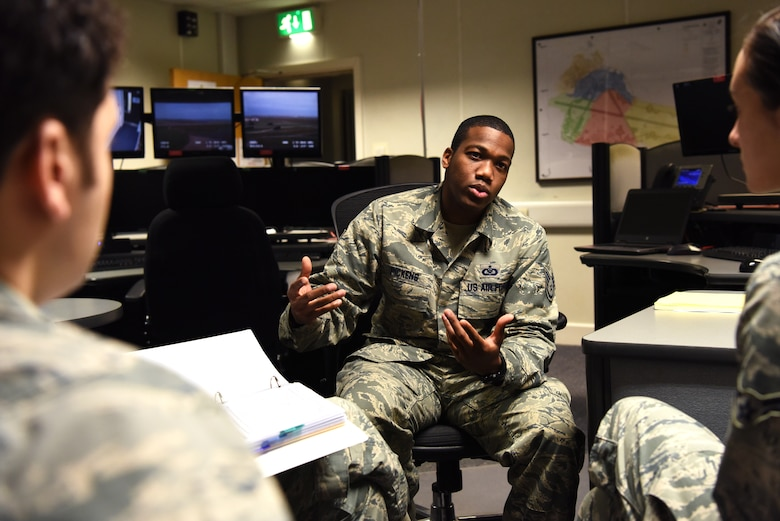 U.S. Air Force Staff Sgt. Justin Pickens, 100th Air Refueling Wing Command Post NCO-in-charge of command and control training, discusses operational checklists with new Airmen in the command post at RAF Mildenhall, England, Nov. 27, 2018. The command post serves as the nerve center from which base leadership monitor and manage the readiness and response of various wings. (U.S. Air Force photo by Airman 1st Class Brandon Esau)