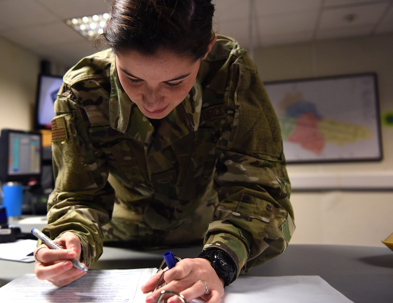 U.S. Air Force Airman 1st Class Kalie Lyons, 100th Air Refueling Wing Command Post emergency action controller, signs off on a controller checklist in the command post at RAF Mildenhall, England, Nov. 27, 2018.  Emergency action controllers are responsible for receiving and disseminating information during emergencies. (U.S. Air Force photo by Airman 1st Class Brandon Esau)