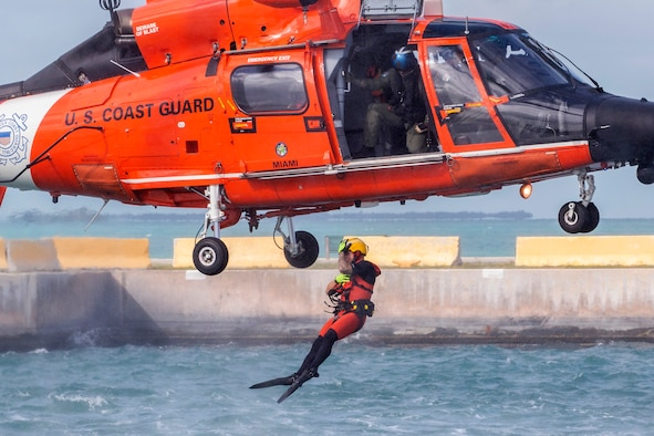 A U.S. Coast Guard rescue swimmer assigned to Air Station Miami jumps out of a, MH-65D Dolphin helicopter to simulate assisting an Airman with the 514th Air Mobility Wing during water survival training at Naval Air Station Key West's Truman Harbor, Key West, Florida, Nov. 16, 2018.
