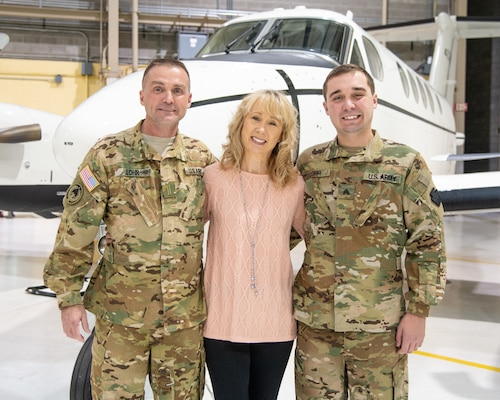 U.S. Army Chief Warrant Officer 5 Jeffrey Lohr, a C-12 master aviator and certified flight instructor assigned to Detachment 28 Operational Support Airlift Command, West Virginia Air National Guard in Williamstown, W.Va.,  poses with his wife Vicki Lynn and son Sgt. Nicholas Lohr, a crew chief with Company C, 1/150th Assault Battalion in Wheeling, W.Va., at the conclusion of his promotion ceremony held Nov. 16, 2018, at the West Virginia National Guard Armory in Williamstown, W.Va.