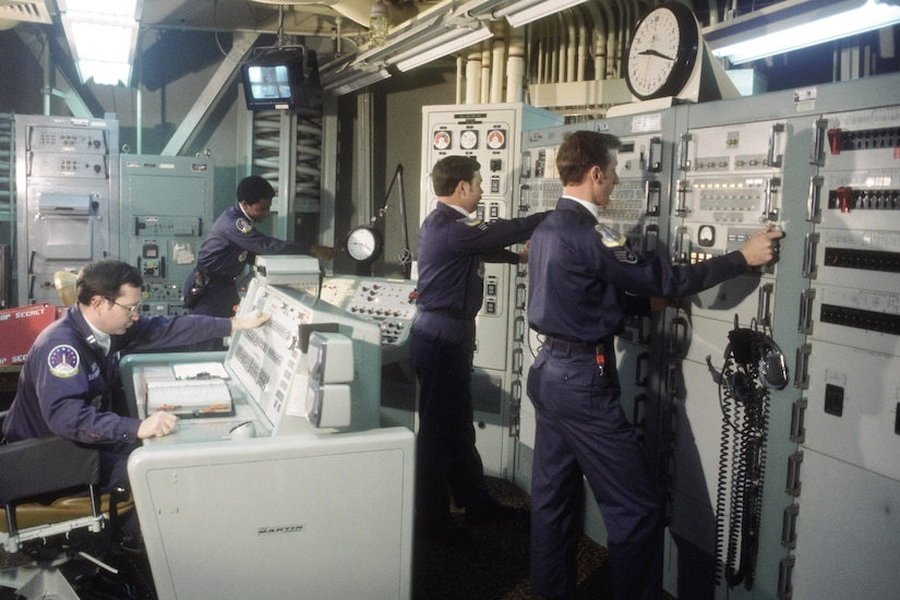 Missile crew members push buttons on Cold War-era equipment.