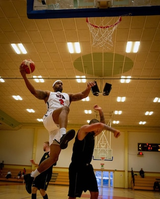 United States Armed Forces Basketball Team member Derell Henderson shoots over Belgian Team's defense in the first game of the 2018 SHAPE International Basketball Tournament, Belgium, November 26, 2018. The annual event brings together teams from around the world for friendly competition and partnership at a prominent NATO installation.(U.S. Air Force photo by Broadcast Journalist Senior Airman Hannah Malone) — at Shape Sports & Fitness Centre.