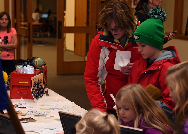 Families who attended a candlelight vigil for the Dean family stop to view a memorial table November 28, 2018, in St. Timothy's Catholic Church, in Manvel, North Dakota. Staff Sgt. Anthony James Dean, his wife Chelsi Kay Dean, and their two children Kaytlin Merie Dean, 5, and Avri James Dean, 1, were killed in a vehicle accident near Billings, Montana, during the Thanksgiving Holiday. (U.S. photo by Airman 1st Class Elora J. Martinez)
