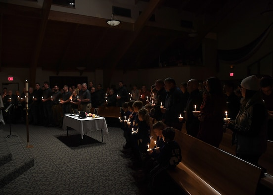 A crowd of nearly 100 people to include families, friends and coworkers from Grand Forks Air Force Base, the Manvel Fire Department and members of the local communities, stand in silence to honor the memories of the Dean family during a vigil hosted November 28, 2018, in St. Timothy's Catholic Church, in Manvel, North Dakota. Staff Sgt. Anthony James Dean, his wife Chelsi Kay Dean, and their two children Kaytlin Merie Dean, 5, and Avri James Dean, 1, were all killed in a vehicle accident during the Thanksgiving holiday near Billings, Montana. The family was spoken of with love, and remembered by the stories shared of their significant involvement in the community. (U.S. photo by Airman 1st Class Elora J. Martinez)