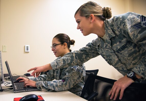 U.S. Air Force Senior Airman Amber Durrence, right, a 6th Medical Operations Squadron mental health technician, shows another Airman how to complete the mental health examination of their pre-deployment process at MacDill Air Force Base, Fla., Nov. 29, 2018.