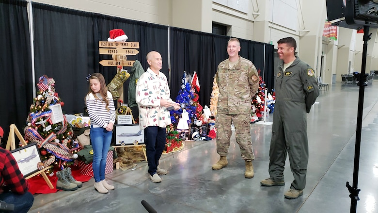 A local TV reporter interviews Senior Master Sgt. Christopher Cain and Lt. Col. Nathan Litz during the Festival of Trees event Nov. 28 in Sandy, Utah, along with Litz's daughter, Gracie