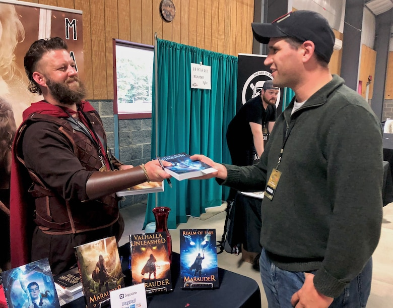 "Former Marine LCpl. David Roach, author of the ""Marauder"" Viking fantasy series, hands his new book, ""Runebinder"" to Navy Lt. Rosert Pfeiffer, Office Naval Intelligence, Washington, D.C., at Vikings Con in LaPlata, Maryland, Oct. 20, 2018."