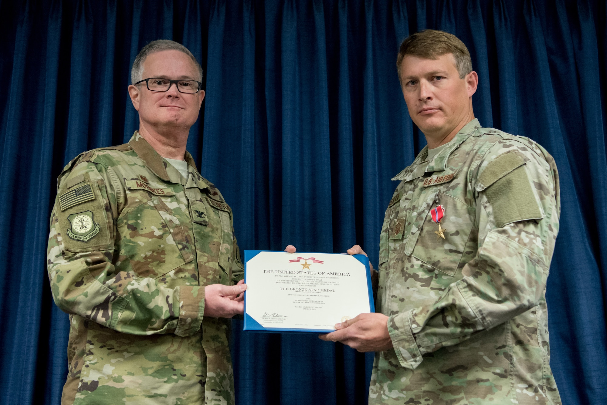 Master Sgt. Benjamen K. Pelster (right), a combat controller for the 123rd Special Tactics Squadron, receives the Bronze Star Medal from Col. David Mounkes, commander of the 123rd Airlift Wing, during a ceremony at the Kentucky Air National Guard Base in Louisville, Ky., Nov. 17, 2018. Pelster was instrumental in the execution of nine missions across five countries involving seven landing zones, nine forward area refueling point surveys and one drop zone certification in 2014. His efforts led to the establishment and expansion of critical air infrastructure in support of Operation Inherent Resolve and across the United States Air Forces Central Command's area of responsibility. (U.S. Air National Guard photo by Staff Sgt. Joshua Horton)