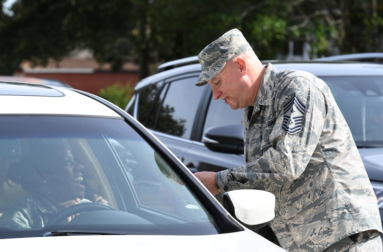 U.S. Air Force Chief Master Sgt. David Pizzuto, 81st Training Wing command chief, checks the ID card of Staff Sgt. Kirshell LaCroix, 81st Contracting Squadron contract specialist, prior to entering Keesler Air Force Base, Mississippi, Nov. 28, 2018. Keesler chief master sergeants assisted the 81st Security Forces Squadron to alleviate the lunch-time traffic and to welcome personnel to the base. (U.S. Air Force photo by Kemberly Groue)