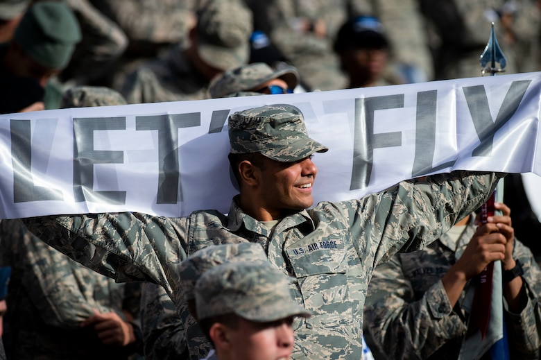 "A cadet holds a banner that reads ""let's fly"""