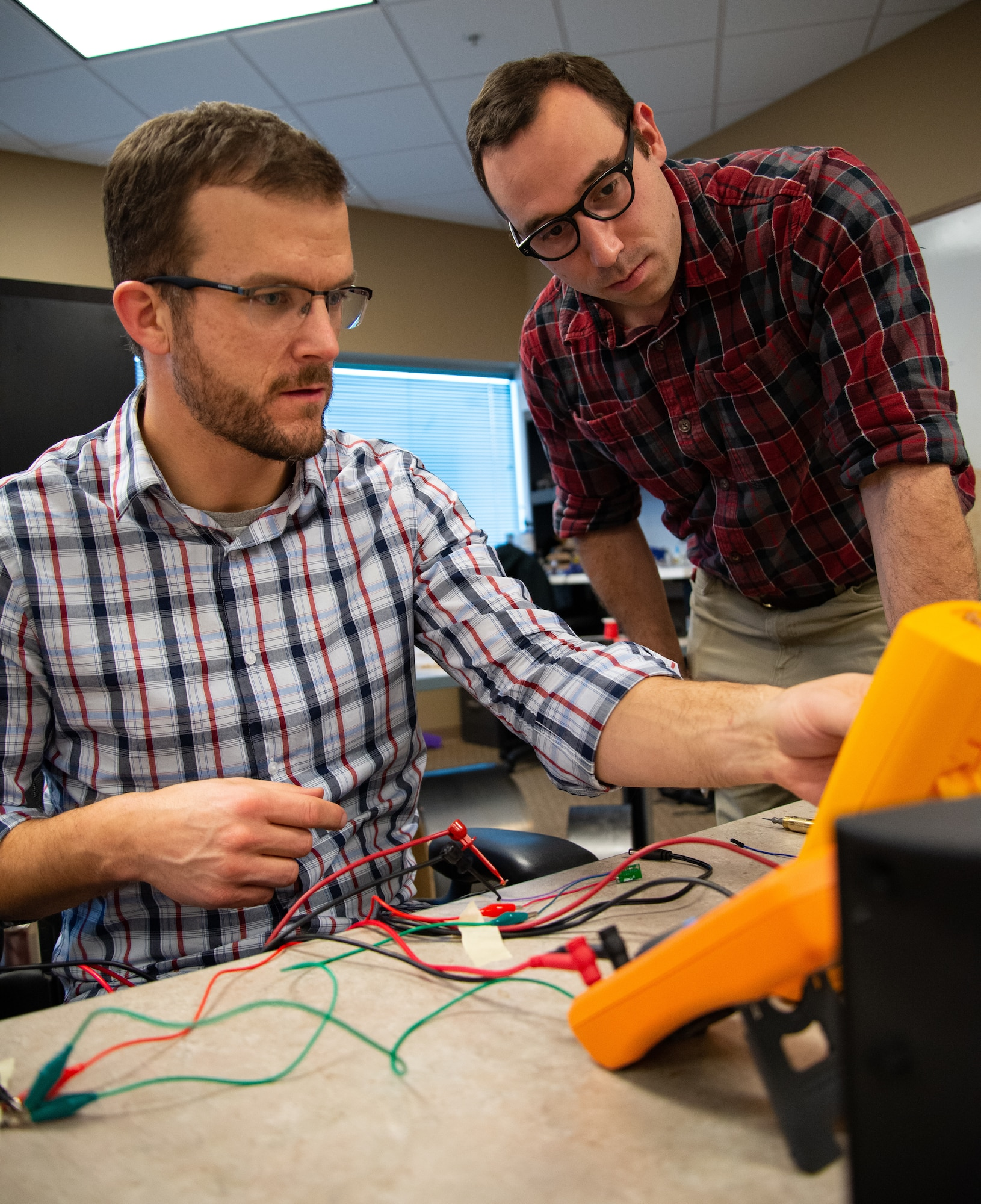 Joe Althaus, Wright Brothers Institute Rapid Innovation Program Manager (left), determines the power consumption of a piece of equipment as Isaac Weintraub, an electronics engineer with Air Force Research Laboratory's Aerospace Systems Directorate, observes during a rapid innovation session at AFRL's Maker Hub.