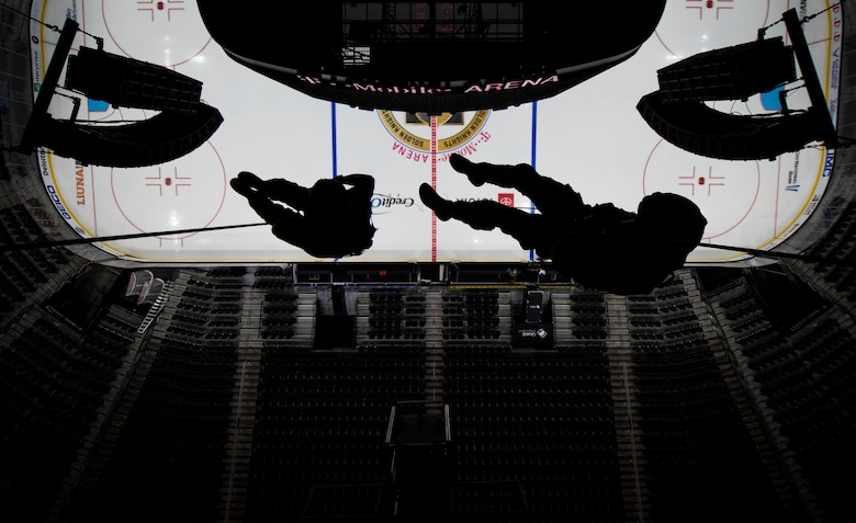 Two pararescuemen rappel over an arena