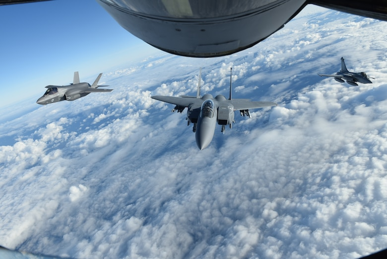 A Royal Air Force F-35 Lightning II, U.S. Air Force F-15E Strike Eagle, and French air force Dassault Rafale fly behind a U.S. Air Force KC-135 Stratotanker