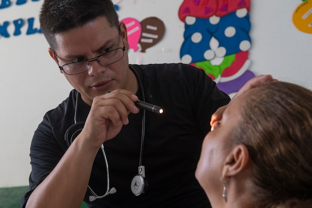 Walter Naira, a doctor in the Honduran navy, examines a patient for the general medicine department at one of two medical sites.
