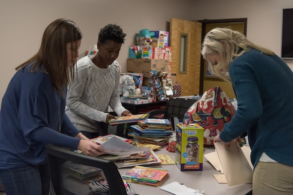 Angela Durham, left, Kareen Kruzelnick and Shannon Manion sort books and donations for a gift drive Nov. 29, 2018, at Offutt Air Force Base, Nebraska.