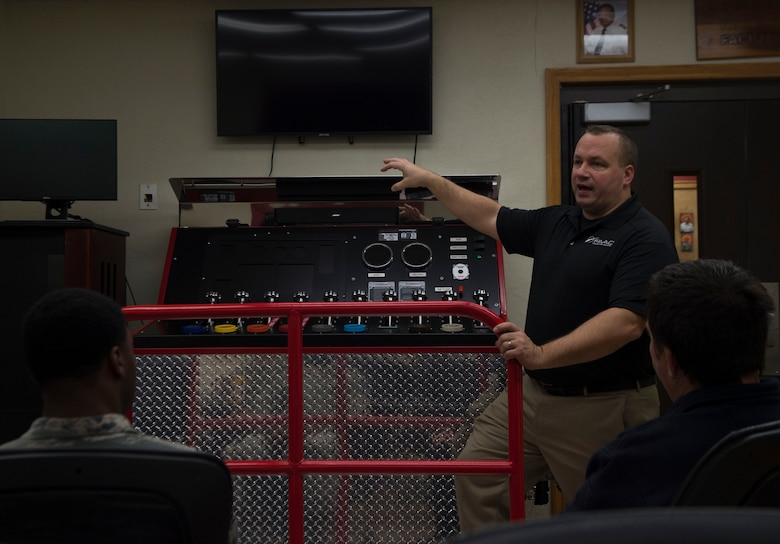 Phil Duczyminski, a subject matter specialist for FAAC, a firefighting simulation company, talks to the 97th Air Mobility Wing Fire Department about how to operate their new pump operations simulator, Nov. 20, 2018, Altus Air Force Base, Okla. This is one of three simulators the fire department is receiving to help make training easier and more efficient. (U.S. Air Force photo by Airman First Class Jeremy Wentworth)