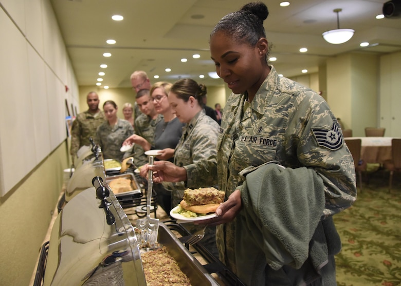 U.S. Air Force Tech. Sgt. Esi Jackson, 81st Dental Squadron dental logistics NCO in charge, places a serving of poyha, a venison dish handed down from the Cherokee tribe, on her plate during the Native American Heritage Month Food Tasting at Keesler Air Force Base, Mississippi, Nov. 29, 2018. The event was held in celebration of Native American Heritage Month. (U.S. Air Force photo by Kemberly Groue)