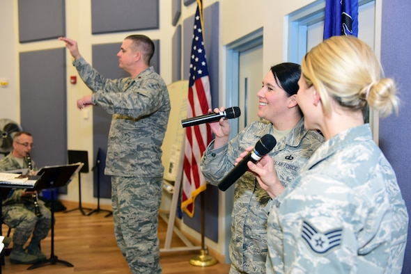 Tech. Sgt. Amy Chicavich (center) and Staff Sgt. Megan May (right), vocalists with the Air National Guard Band of the Northeast, and Maj. Joseph Denti (left), commander and conductor of the band, rehearse Nov. 17, 2018, for the band's annual holiday concert. The concert is scheduled for Dec. 16 at the Auditorium of the Scottish Rite Cathedral, Harrisburg, Pennsylvania, at 3 p.m. and will feature the 35-piece wind-ensemble Concert Band performing several winter and holiday-themed songs. (U.S. Air National Guard photo by Tech. Sgt. Claire Behney/Released)