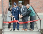 four people cut a ribbon in front of a building