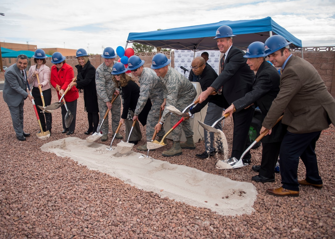 Leaders from Coral Academy of Science Las Vegas, Nellis Air Force Base, Nev. and the local community shovel sand during the Coral Academy groundbreaking ceremony on Nellis AFB, Nev., Nov. 28, 2018. The new school will replace the current Nellis AFB facility that was constructed in 1952. (U.S. Air Force photo by Airman 1st Class Dylan T. Murakami)