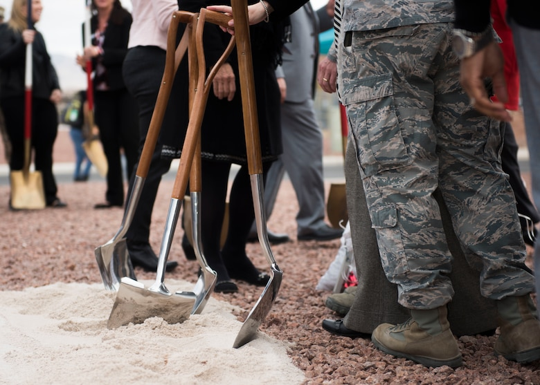 Leaders from Coral Academy of Science Las Vegas, Nellis Air Force Base, Nev. and the local community rest their shovels in sand during the Coral Academy groundbreaking ceremony on Nellis AFB, Nev., Nov. 28, 2018. The ceremony celebrated the start of construction for CASLV's on-base campus. (U.S. Air Force photo by Airman 1st Class Dylan T. Murakami)