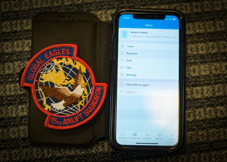 A 15th Airlift Squadron patch next to a smartphone with the squadrons scheduling application interface Nov. 30, 2018, at Joint Base Charleston, S.C. The 15th AS decided to employ an innovative and efficient way of relaying scheduling information to the flyers via a smartphone application.