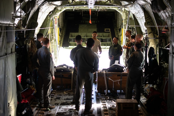 36th Airlift Squadron loadmasters discuss low-cost, low-altitude bundle rigging procedures in preparation for Operation Christmas Drop at Yokota Air Base, Japan Nov, 16, 2018. OCD is the longest running Department of Defense humanitarian airlift training operation and will provide nearly 25 tons of critical supplies to 56 Micronesian Islands this year impacting about 20,000 people. (U.S. Air Force photo by Tech. Sgt. Michael Smith)